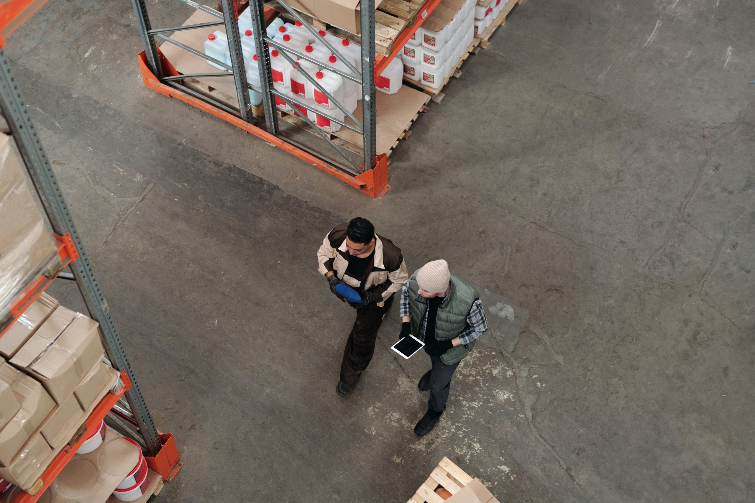 Two men walking through a distribution warehouse working on mobile tablets
