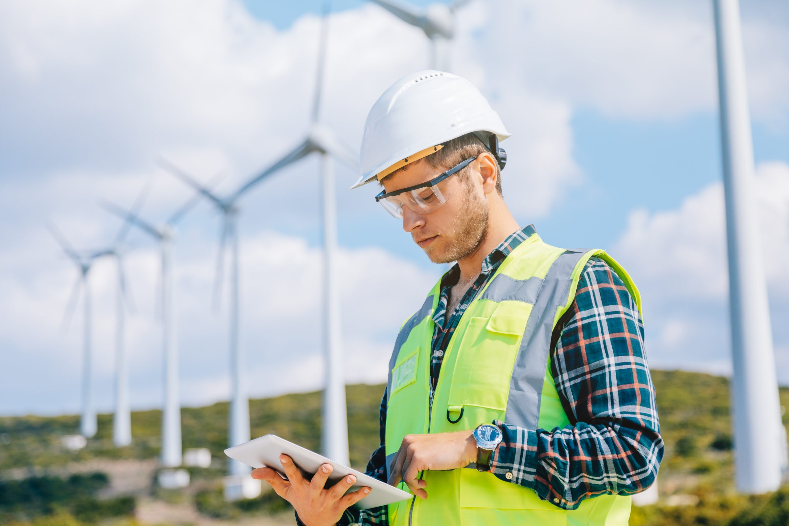 Employee in a safety vest and hard hat working on a tablet on a wind and energy farm